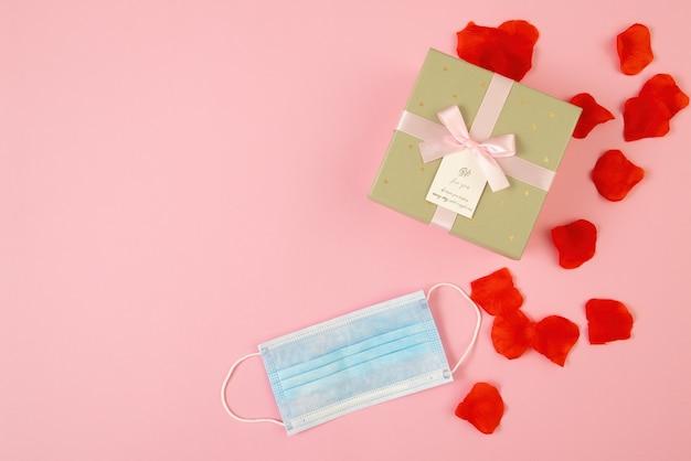 Presente su sfondo rosa con mascherina chirurgica blu in una composizione piatta