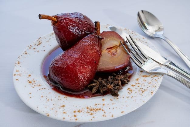Presentazione di due pere al vino rosso con una tagliata al centro su un piatto bianco con la salsa al vino. vista ravvicinata,