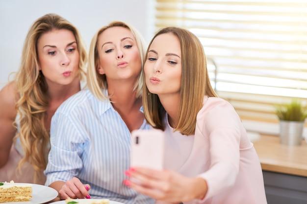 Presentando un felice gruppo di amici usando lo smartphone