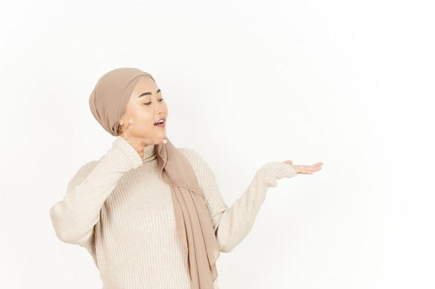 Presentazione del prodotto sul palmo aperto della bella donna asiatica che indossa l'hijab isolato su sfondo bianco