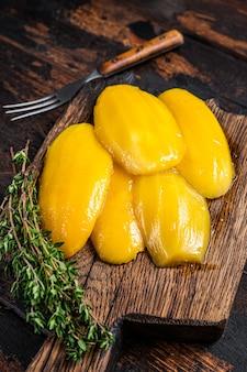 Conserva le fette di mango su una tavola di legno