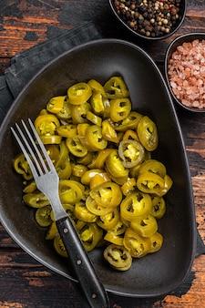 Jalapenos conservati, in salamoia e affettati nel piatto. fondo di legno scuro. vista dall'alto.