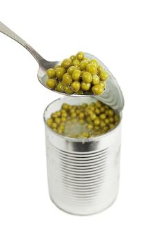 Verdure conservate di piselli in primo piano del cucchiaio di metallo isolato su uno sfondo bianco