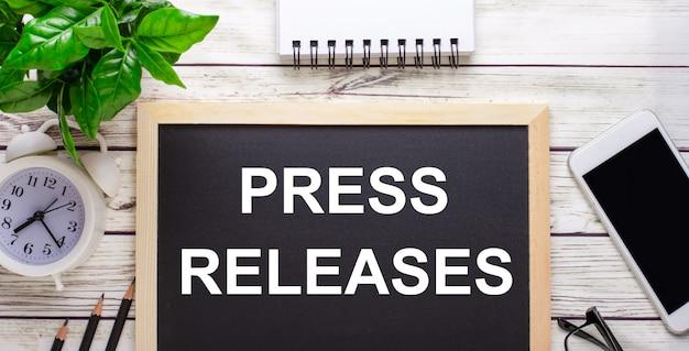 Comunicati stampa scritti su una superficie nera vicino a matite, uno smartphone, un blocco note bianco e una pianta verde in un vaso