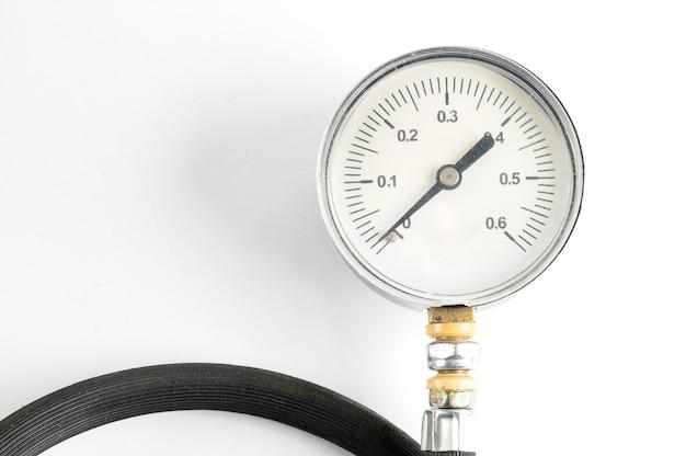 Manometro per misurare la pressione dell'aria nel primo piano di pneumatici per automobili su un bianco isolato