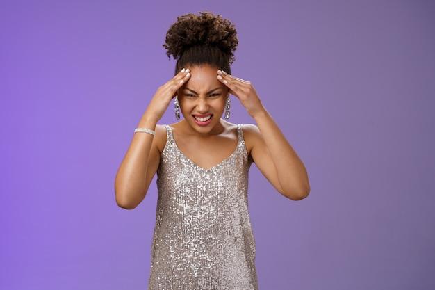 Donna afroamericana preoccupata intensa e sotto pressione in abito scintillante d'argento che fa smorfie e si rattrista dolore...