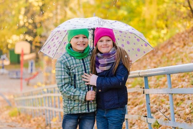 Ragazzo e ragazza del preteen che camminano al parco di pioggia