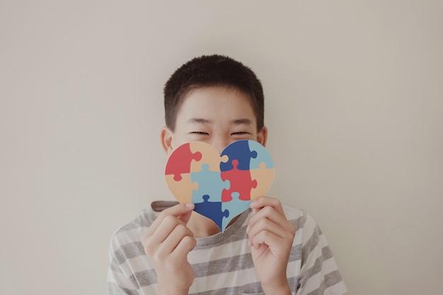 Ragazzo del preteen che tiene puzzle jigsaw, salute mentale del bambino, giornata mondiale della consapevolezza dell'autismo
