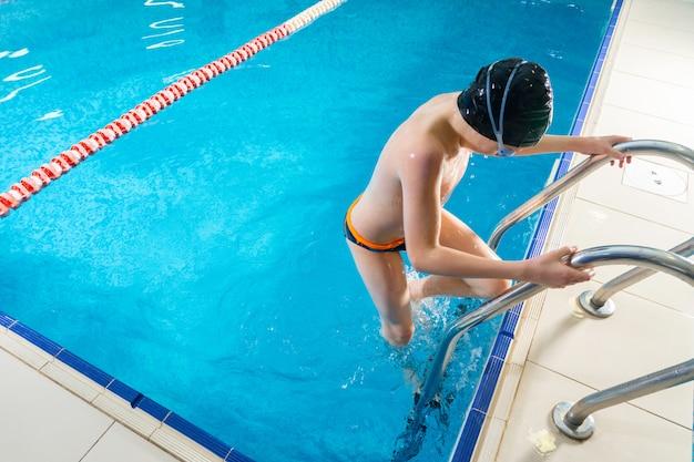 Nuoto del ragazzo del preteen nello stagno dell'interno durante la lezione di nuoto