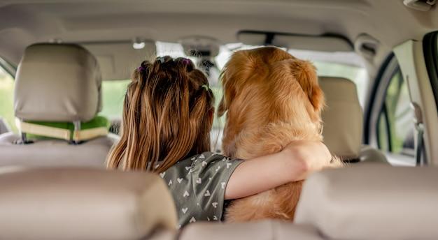 Preteen ragazza che abbraccia il cane golden retriever e seduto in macchina all'interno. bambino con cagnolino di razza nel veicolo da dietro