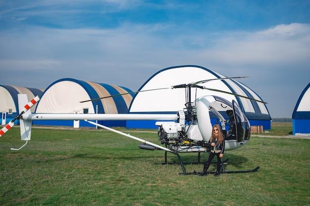 Preteen ragazza in occhiali da sole in piedi vicino all'elicottero nel campo di volo