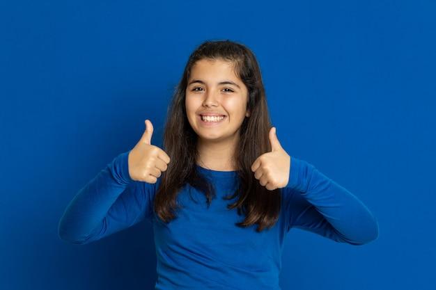 Ragazza del preteen con la maglia blu che gesturing sopra la parete blu