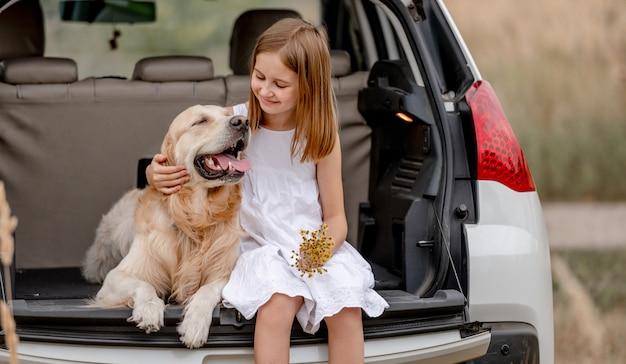 Ragazza del preteen con il cane del documentalista dorato che si siede insieme nel bagagliaio di un'auto. bambino grazioso che abbraccia l'animale domestico del cagnolino nel veicolo