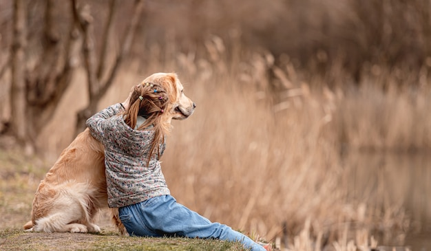 Ragazza preadolescente con cane golden retriever