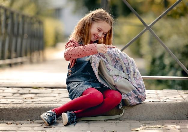 Preteen school girl cercando in zaino, seduto a terra e sorridente. dolce pupilla bambina che riposa dopo la lezione di educazione nel parco autunnale