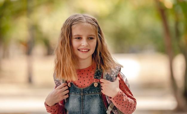 Ragazza della scuola del preteen con il ritratto del primo piano dello zaino all'aperto. graziosa allieva bambina dopo la lezione di educazione nel parco autunnale