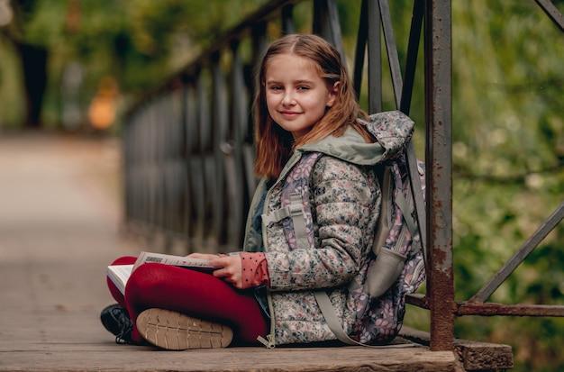 Preteen scuola ragazza con zaino seduto a terra e leggere il libro all'aperto. bambina dolce allieva che studia nel parco autunnale