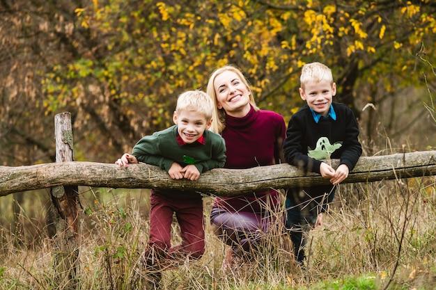 Preteen gemelli biondi fratelli che giocano all'aperto con felice mamma single al bellissimo caldo parco autunnale, weekend in famiglia nella natura