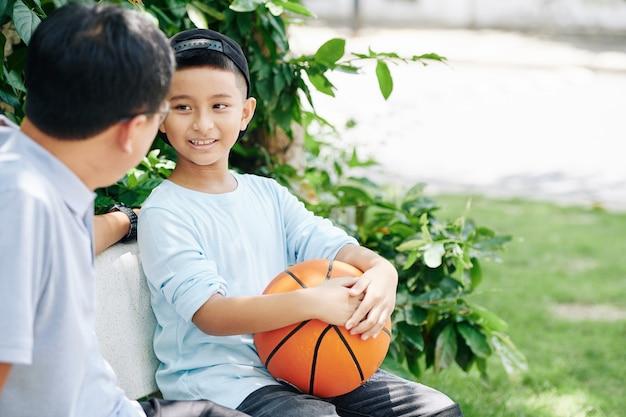 Preteen ragazzo vietnamita con la palla da basket a parlare con il padre quando è seduto su una panchina dopo la partita