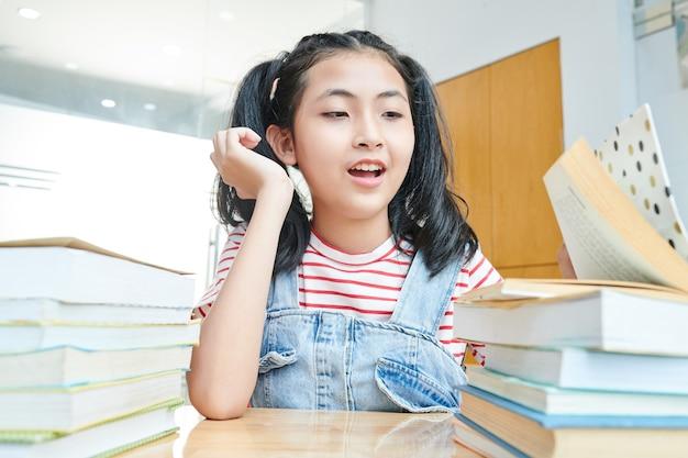 Preteen ragazza vietnamita guardando molti libri sulla sua scrivania