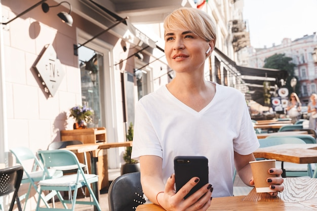 Bella donna adulta che indossa una maglietta bianca tramite telefono cellulare e auricolare wireless, mentre è seduto in un bar all'aperto in estate e beve caffè dal bicchiere di carta