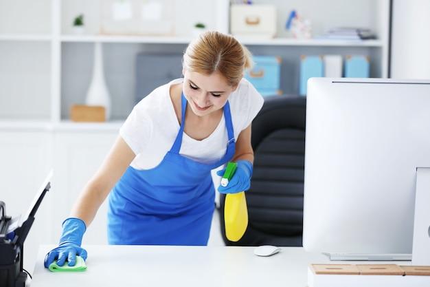 Donna abbastanza adulta che pulisce la tabella in ufficio