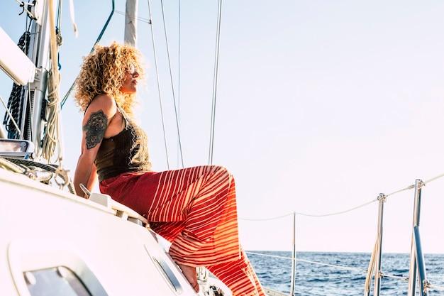 La donna graziosa adulta sullo yacht nel lusso si rilassa lo stile di vita godendosi il viaggio e l'oceano blu