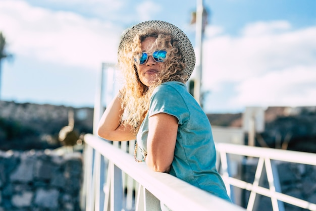 La giovane donna graziosa adulta sorride e gode delle attività di svago all'aperto nella giornata di sole