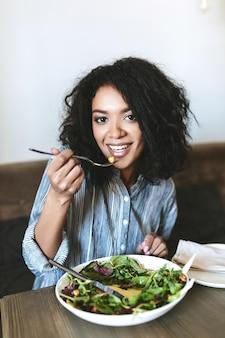 Ragazza abbastanza afroamericana che mangia insalata nel ristorante. ritratto di signora sorridente con capelli ricci scuri e insalata sul tavolo al caffè