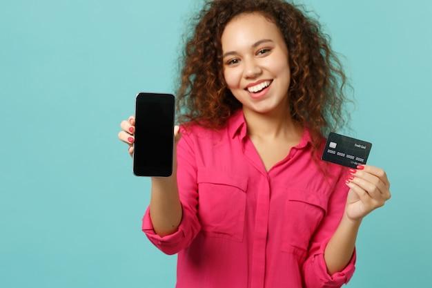 La ragazza abbastanza africana in abbigliamento casual tiene il telefono cellulare con lo schermo vuoto in bianco, carta bancaria di credito isolata su fondo blu del turchese. persone sincere emozioni, concetto di stile di vita. mock up copia spazio.
