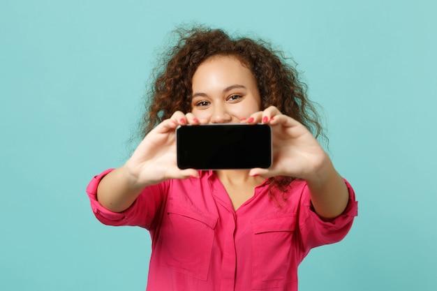 La ragazza abbastanza africana in vestiti casuali tiene il telefono cellulare con lo schermo vuoto in bianco isolato sul fondo blu della parete del turchese in studio. persone sincere emozioni, concetto di stile di vita. mock up copia spazio.