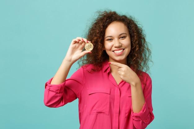 Bella ragazza africana in abiti casual che punta il dito indice su bitcoin valuta futura isolata su sfondo blu turchese in studio. concetto di stile di vita di emozioni sincere della gente. mock up copia spazio.