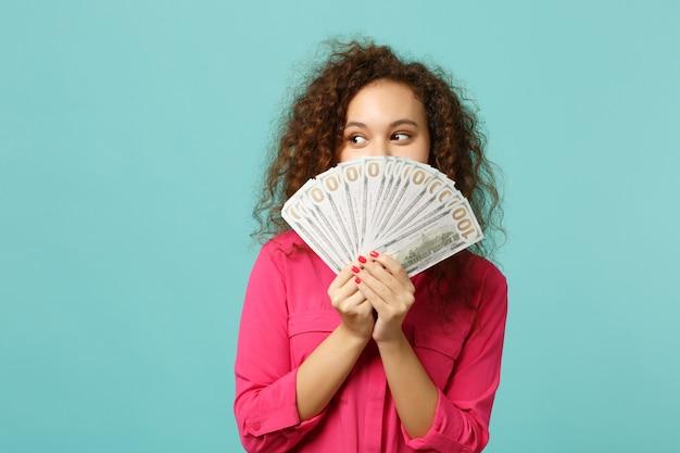 Bella ragazza africana che copre il viso con un ventaglio di soldi in banconote in dollari, denaro contante isolato su sfondo blu turchese parete in studio. concetto di stile di vita di emozioni sincere della gente. mock up copia spazio.