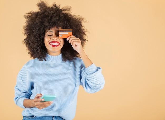 Bella donna afroamericana che acquista online, telefono cellulare e carta di credito che copre un occhio