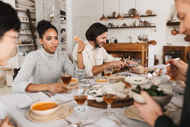 Pretty afro american donna seduta al tavolo a parlare pensieroso mentre l'uomo vicino felicemente il taglio del pane