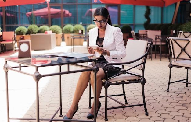 Donna abbastanza afro di affari in una giacca bianca che si siede nel caffè all'aperto e usa lo smartphone