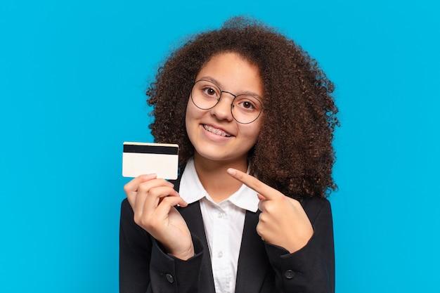 Ragazza abbastanza afro di affari dell'adolescente con una carta di credito. concetto di acquisto online