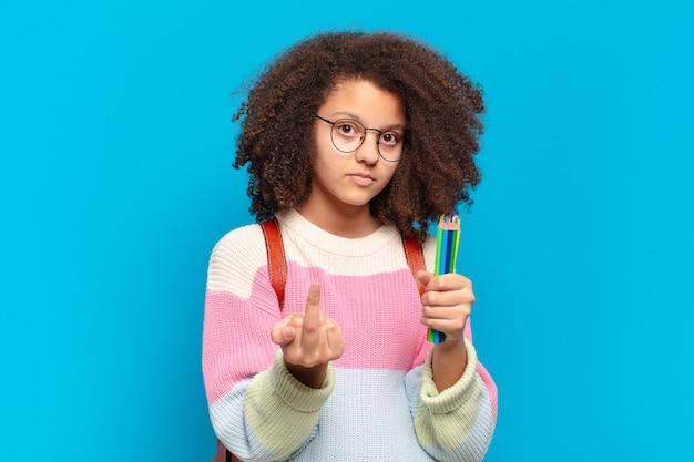 Adolescente abbastanza afro che si sente arrabbiato, infastidito, ribelle e aggressivo, lancia il dito medio, reagisce. concetto di studente