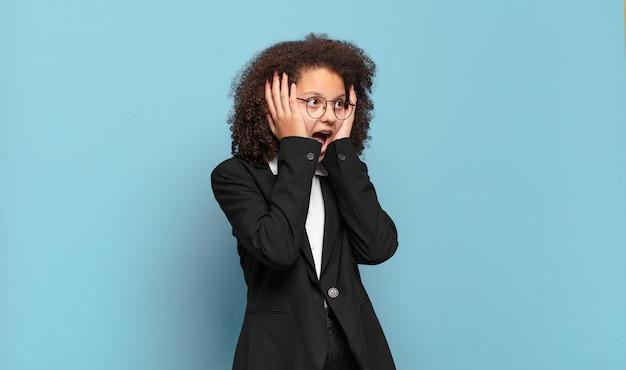 Adolescente abbastanza afro che si sente felice, eccitato e sorpreso, guardando di lato con entrambe le mani sul viso. concetto di business umoristico