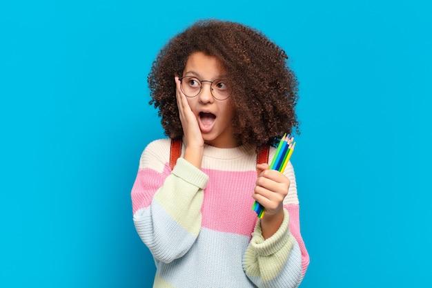 Adolescente abbastanza afro che si sente felice, eccitato e sorpreso, guardando di lato con entrambe le mani sul viso. concetto di studente
