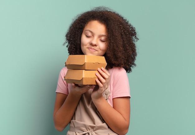 Cuoco unico della ragazza dell'adolescente abbastanza afro con scatole di hamburger da asporto