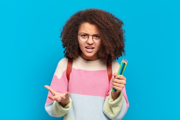 Adolescente abbastanza afro che sembra arrabbiato, infastidito e frustrato urlando wtf. concetto di studente
