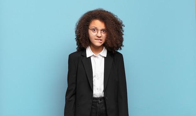 Adolescente abbastanza afro che sembra perplesso e confuso, mordendosi il labbro con un gesto nervoso, non conoscendo la risposta al problema. concetto di business umoristico
