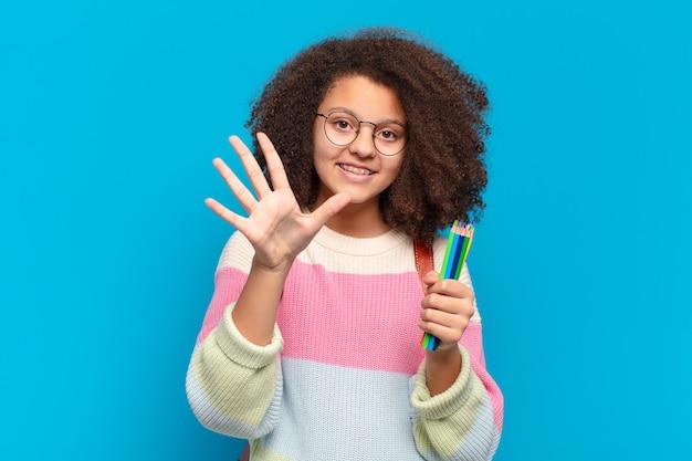 Adolescente abbastanza afro che sorride e sembra amichevole, mostrando il numero cinque o quinto con la mano in avanti, contando alla rovescia. concetto di studente