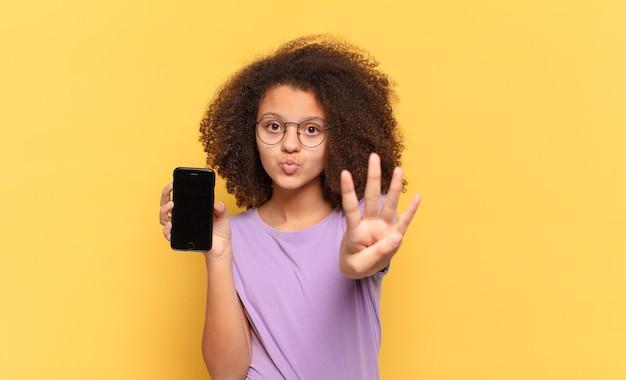Adolescente abbastanza afro che sorride e sembra amichevole, mostrando il numero quattro o il quarto con la mano in avanti, il conto alla rovescia e tenendo una cella