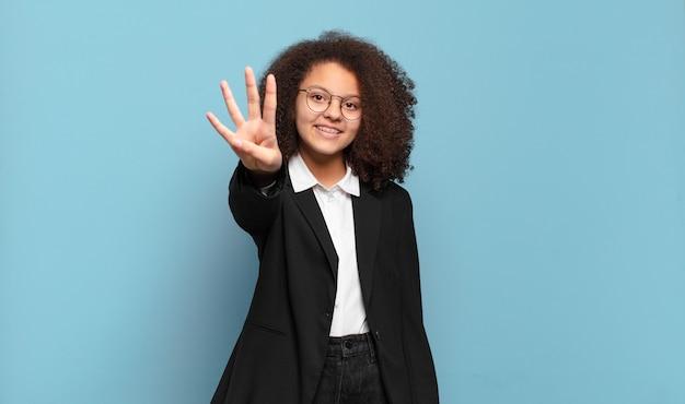 Adolescente abbastanza afro che sorride e sembra amichevole, mostrando il numero quattro o il quarto con la mano in avanti, contando alla rovescia. concetto di business umoristico