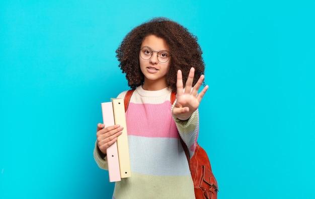 Adolescente abbastanza afro che sorride e sembra amichevole, mostrando il numero quattro o il quarto con la mano in avanti, contando alla rovescia. concetto di studente
