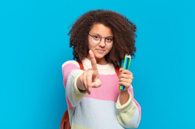 Adolescente abbastanza afro che sorride e sembra amichevole, mostrando il numero uno o il primo con la mano in avanti, contando alla rovescia. concetto di studente