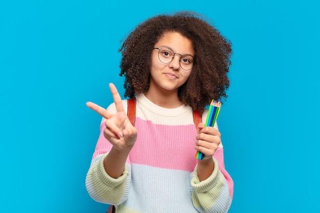 Adolescente abbastanza afro che sorride e sembra amichevole, mostrando il numero due o il secondo con la mano in avanti, contando alla rovescia. concetto di studente