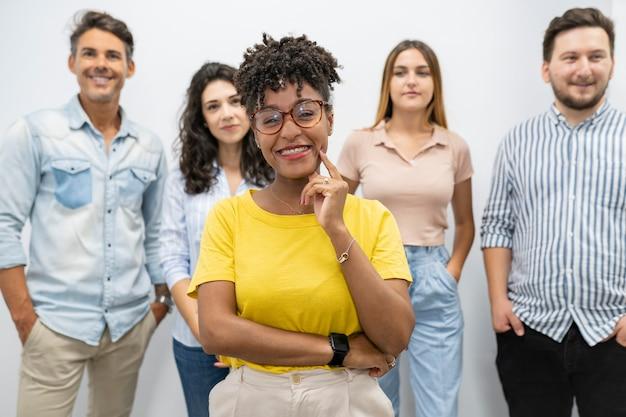 Bella donna afro in coworking con i suoi colleghi dietro, capo